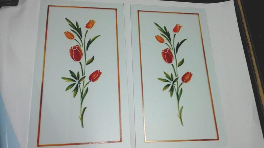 Lavorazione di due vetri satinati con decoro floreale scavato e colorato